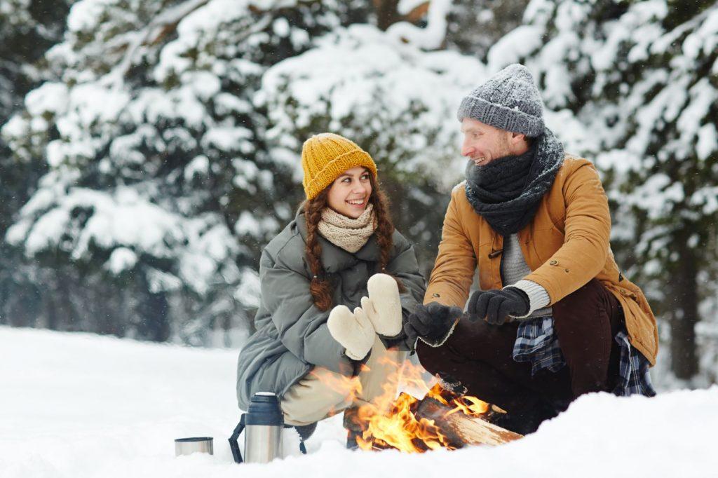 two people keeping warm near a bonfire