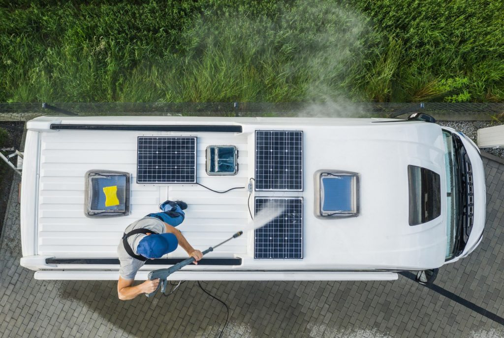 man cleaning his rv roof
